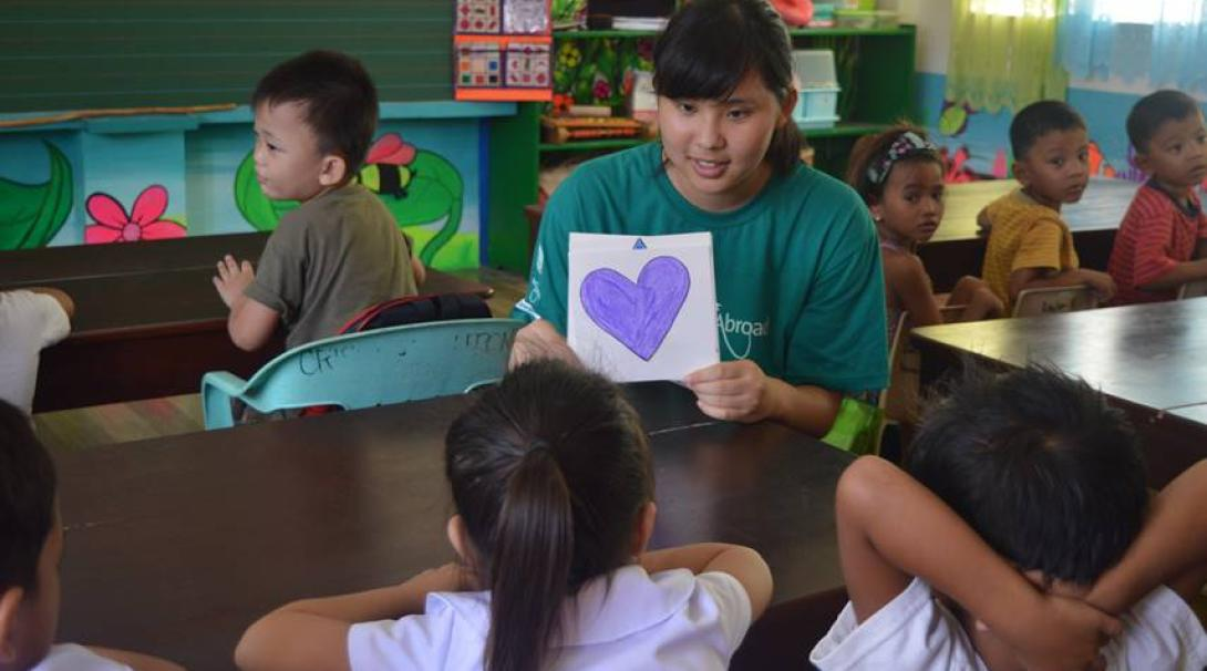 A Projects Abroad volunteer showing Filipino children a purple heart as part of identifying basic shapes